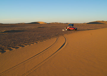 A camping spot at the base of a sand dune.